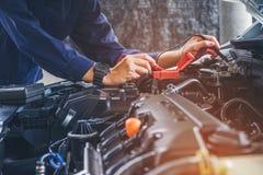 Handen die van autowerktuigkundige in de autoreparatiedienst werken