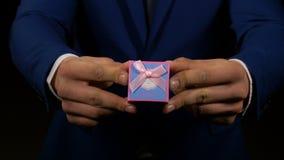Handen die van de mens en de kleine doos van giftjuwelen tonen houden stock footage
