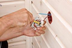 Handen die van een elektricien die een contactdoos installeren, een close-up verwijderen royalty-vrije stock fotografie