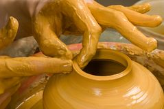 Handen die van een pottenbakker, tot een aarden kruik gele klei leiden stock foto