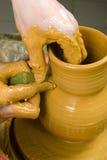 Handen die van een pottenbakker, tot een aarden kruik gele klei leiden royalty-vrije stock foto's