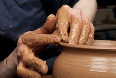 Handen die van een pottenbakker, tot een aarden kruik leiden royalty-vrije stock foto's
