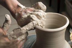 Handen die van een pottenbakker, tot een aarden kruik leiden royalty-vrije stock afbeeldingen