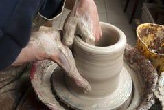Handen die van een pottenbakker, tot een aarden kruik leiden Stock Afbeelding