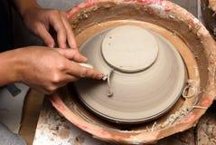 Handen die van een pottenbakker, tot een aarden kruik leiden stock fotografie