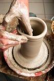 Handen die van een pottenbakker, tot een aarden kruik leiden Stock Foto