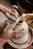 Handen die van een pottenbakker, tot een aarden kruik leiden Royalty-vrije Stock Foto