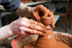 Handen die van een pottenbakker, tot een aarden kruik leiden stock afbeeldingen