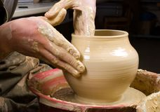 Handen die van een pottenbakker, tot een aarden kruik leiden stock foto's