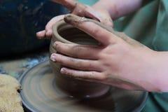 Handen die van een pottenbakker, tot een aarden kruik op aardewerkwiel leiden stock fotografie