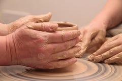 Handen die van een pottenbakker, tot een aarden kruik op aardewerkwiel leiden stock foto