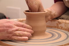 Handen die van een pottenbakker, tot een aarden kruik op aardewerkwiel leiden stock afbeelding