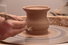Handen die van een pottenbakker, tot een aarden kruik op aardewerkwiel leiden royalty-vrije stock fotografie