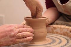 Handen die van een pottenbakker, tot een aarden kruik op aardewerkwiel leiden stock afbeeldingen