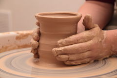 Handen die van een pottenbakker, tot een aarden kruik op aardewerkwiel leiden royalty-vrije stock afbeeldingen
