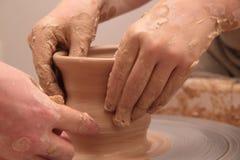 Handen die van een pottenbakker, tot een aarden kruik op aardewerkwiel leiden stock foto's