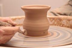 Handen die van een pottenbakker, tot een aarden kruik op aardewerkwiel leiden royalty-vrije stock afbeelding