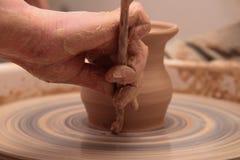 Handen die van een pottenbakker, tot een aarden kruik op aardewerkwiel leiden royalty-vrije stock foto's