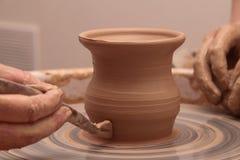 Handen die van een pottenbakker, tot een aarden kruik op aardewerkwiel leiden royalty-vrije stock foto