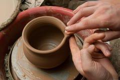 Handen die van een pottenbakker, tot een aarden kruik op de cirkel leiden royalty-vrije stock foto's