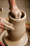 Handen die van een pottenbakker, tot een aarden kruik op de cirkel leiden royalty-vrije stock fotografie