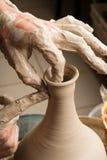 Handen die van een pottenbakker, tot een aarden kruik op de cirkel leiden stock foto