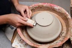 Handen die van een pottenbakker, tot een aarden kruik op de cirkel leiden stock fotografie