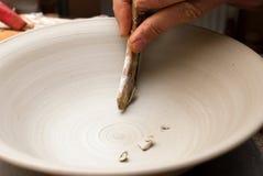 Handen die van een pottenbakker, tot een aarden kruik op de cirkel leiden royalty-vrije stock afbeelding