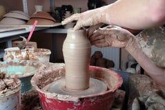Handen die van een pottenbakker, tot een aarden kruik op de cirkel leiden royalty-vrije stock afbeeldingen