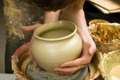 Handen die van een pottenbakker, tot een aarden kruik op de cirkel leiden stock foto's