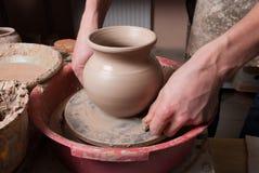 Handen die van een pottenbakker, tot een aarden kruik op de cirkel leiden stock afbeeldingen