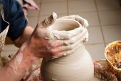Handen die van een pottenbakker, tot een aarden kruik op de cirkel leiden royalty-vrije stock foto