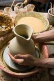 Handen die van een pottenbakker, tot een aarden kruik witte klei leiden royalty-vrije stock fotografie