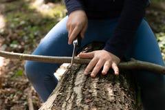Handen die van meisje of jongen die een Zwitsers mes gebruiken, een stuk van hout in het bos zagen, niemand stock foto