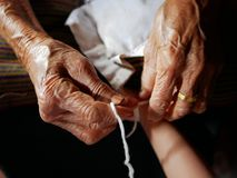 Handen die van oude vrouw een wit koord Sai Sin binden rond haar kleindochterhanden - Thaise traditionele zegen van oudere  stock foto's
