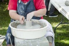 Handen die van vrouwelijke pottenbakker bij het het werpen wiel werken en het vormen royalty-vrije stock foto's