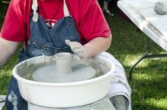 Handen die van vrouwelijke pottenbakker bij het het werpen wiel werken en het vormen stock afbeelding