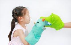 Handen die van weinig de Aziatische kindmeisje dierlijke marionetten met hand van haar moeder op witte achtergrond spelen Onderwi royalty-vrije stock foto