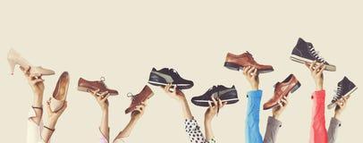 Handen die verschillende schoenen op geïsoleerde achtergrond houden stock foto