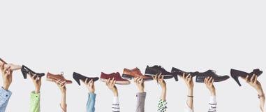 Handen die verschillende schoenen op geïsoleerde achtergrond houden royalty-vrije stock afbeeldingen