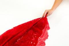Handen drar ett rött tyg med snör åt fotografering för bildbyråer
