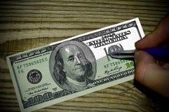 Handen drar räkningen för dollar 100 på en träbakgrund Royaltyfri Foto
