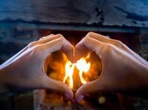 Handen in een hart tegen een open haardachtergrond die worden gevormd Royalty-vrije Stock Fotografie