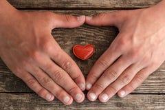 Handen en een rood hart die op een houten achtergrond, concept liggen gezondheid stock fotografie