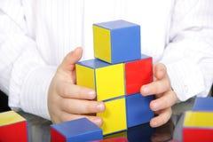 Handen en kleurenbakstenen Stock Foto