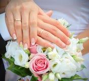 Handen en ringen op huwelijksboeket Royalty-vrije Stock Foto