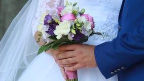 Handen en ringen op huwelijksboeket stock video