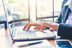 Handen för affärskvinnan fungerar på en bärbar datordator i ett kontor fotografering för bildbyråer