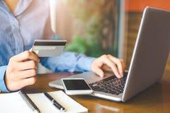 Handen för affärskvinnan rymmer en kreditkort och använder en bärbar datorcomput royaltyfri foto
