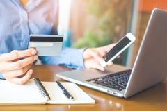 Handen för affärskvinnan rymmer en kreditkort och använder en telefon till royaltyfria bilder